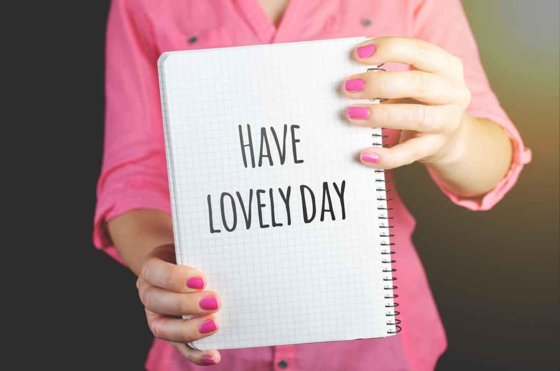 woman wearing pink dress holding graphing notebook with have a lovely day sign