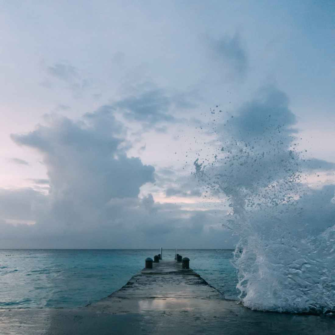 ocean wave splashing on dock